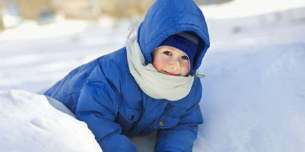 Young boy in blue snow suit laying on snow